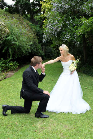Handsome groom kneeling to kiss his beautiful brides hand photo