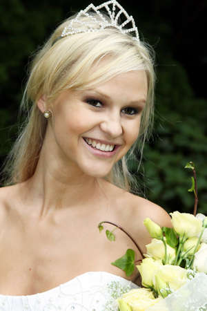 Gorgeous blond bride with bouquet of flowers at the beach photo