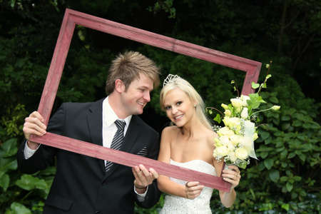 Lovely smiling wedding couple looking through a wooden picture frame