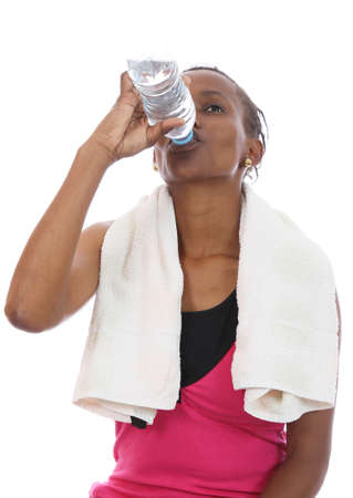 Young African woman drinking water after hard exercise session photo