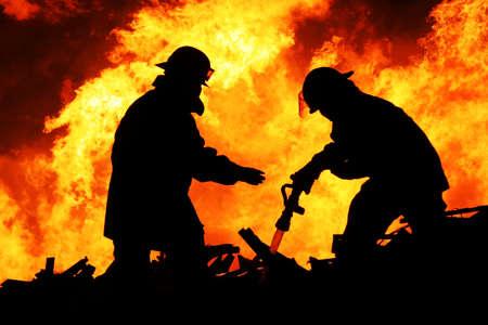 Silhouette dei vigili del fuoco che lottano un incendio con fiamme enormi di legname ardente Archivio Fotografico