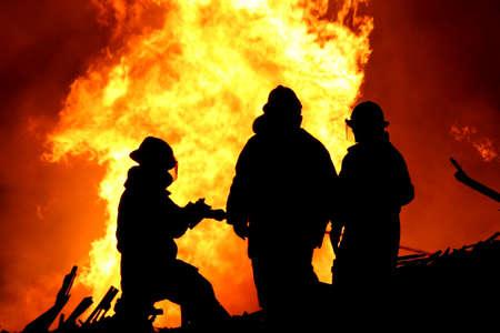 Drei Feuerwehrleute im Kampf mit einem wütenden Feuer mit riesigen Flammen des brennenden Holzes