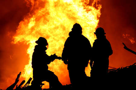 Three firemen fighting a raging fire with huge flames of burning  timber photo
