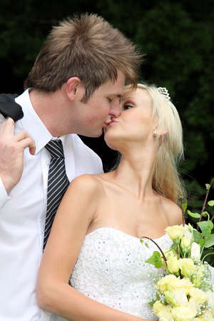 Lovely young couple sharing a kiss on their wedding day photo