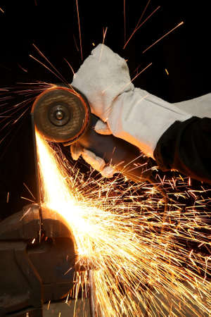 Shower of orange sparks from a worker grinding steel photo