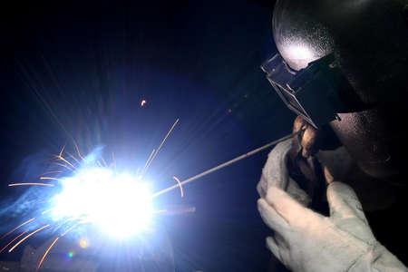 Welder with protective gloves and helmet welding steel Stock Photo - 12392339