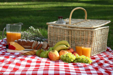 Sumptuous picnic spread out on a red and white checked cloth with wicker basket photo
