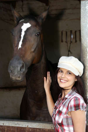 Beautiful smiling brunette woman with her horse in a stable photo