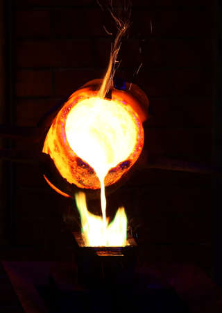 Molten gold being poured to form an ingot bar Stock Photo