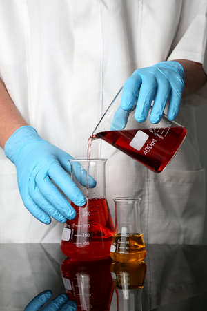 Latex gloved hands pouring liquads into a flask in a laboratory photo