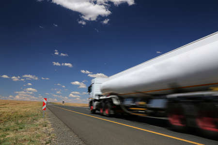 tanks: White tanker truck transporting fuel along the tar highway Stock Photo
