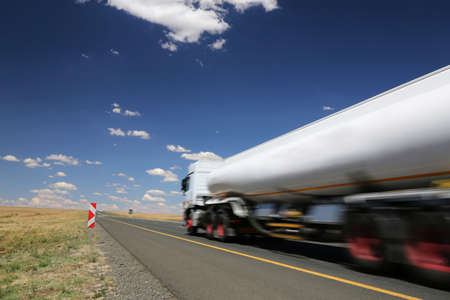 White tanker truck transporting fuel along the tar highway Stock Photo