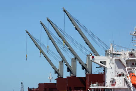 Four large cranes on board a cargo ship photo