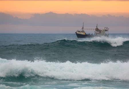 mare agitato: Pesca strascico al largo della costa al largo del Sud Africa al tramonto