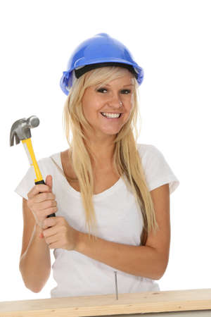 Lovely blond lady hammering in a nail into timber photo