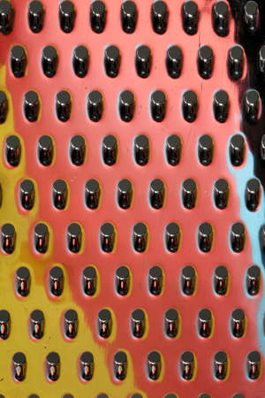 sidelit: Macro view of a stainless steel cheese grater with reflected colors