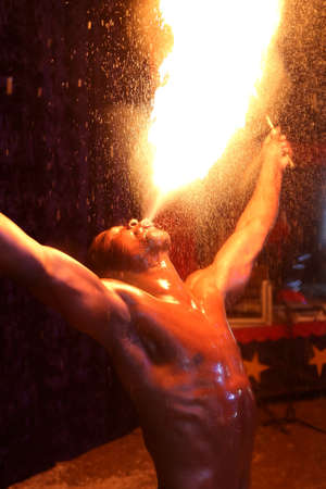 stunts: Circus fire-eater blowing a large flame from his mouth