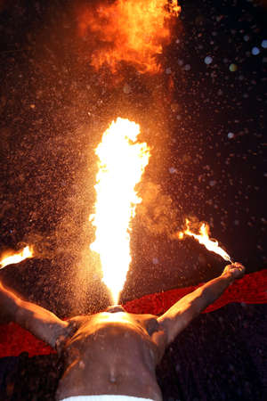 eater: Circus fire-eater blowing a large flame from his mouth
