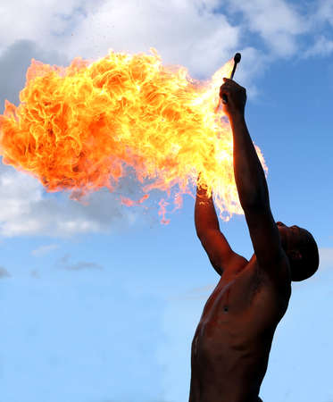 burning man: Circus fire-eater blowing a large flame from his mouth