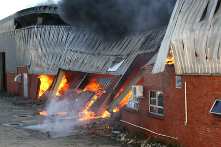 building on fire: Warehouse building burning with intense flames
