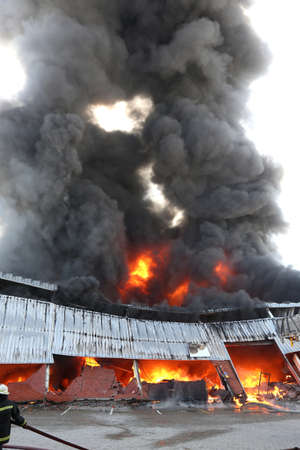 Warehouse building burning with intense flames and fireman attending Stock Photo