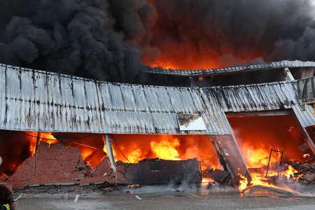 強烈な炎と消防士の参加の燃える建物倉庫します。