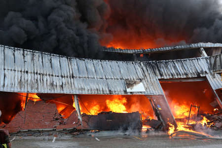 Warehouse building burning with intense flames and fireman attending Imagens