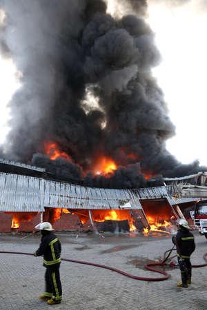 resplandor: Almacén de construcción ardiendo con llamas intensas y bomberos asistiendo