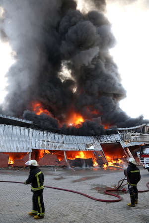 Warehouse building burning with intense flames and fireman attending photo