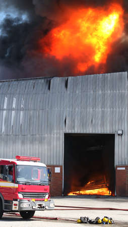 warehouse building: Warehouse building burning with intense flames and firemen attending Stock Photo