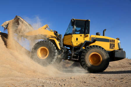 sand quarry: Bulldozer dumping stone and sand in a mining quarry