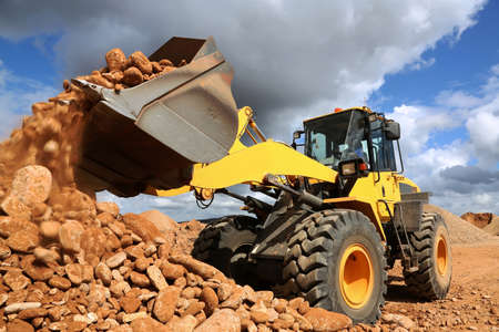 광산 채석장에서 돌과 모래를 덤핑 프런트 엔드 로더 스톡 콘텐츠