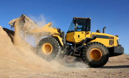 front loader: Pala cargadora vertido de piedra y arena en una cantera minera