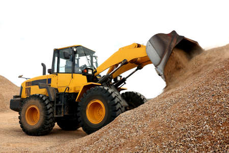 Bulldozer dumping stone and sand in a mining quarry