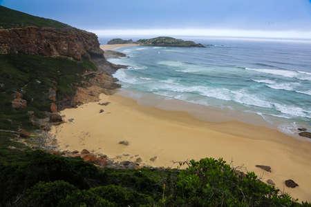 mare agitato: Mare agitato e sabbia dorata sulla costa frastagliata in Sud Africa