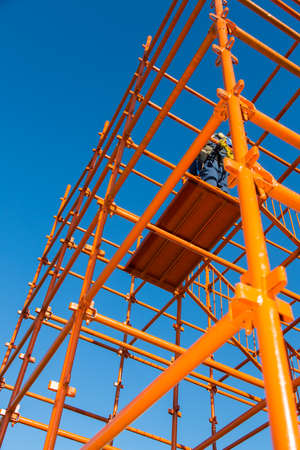 Bright orange scaffolding pipes against a blue sky