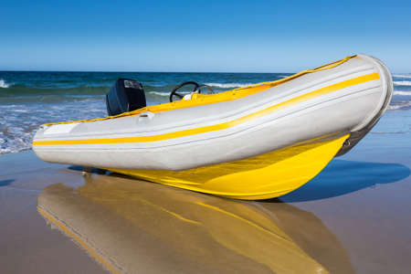 Yellow and white rubber duck inflatable boat on the sandy beach photo
