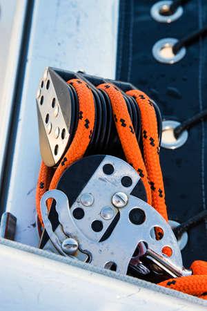poleas: Poleas con roaps naranja y hebillas de acero inoxidable en un yate de vela