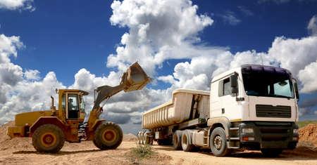 camion minero: Cargador frontal colocando la piedra y la arena en un gran camión o remolque Foto de archivo