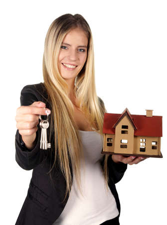house coats: Pretty smiling estate agent woman with keys and model house
