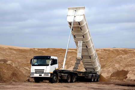 tipping: Huge tipper truck with hydraulic lifter in a sand quarry