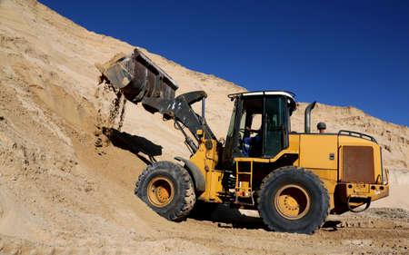 front end loader: Front end loader machine digging up sand