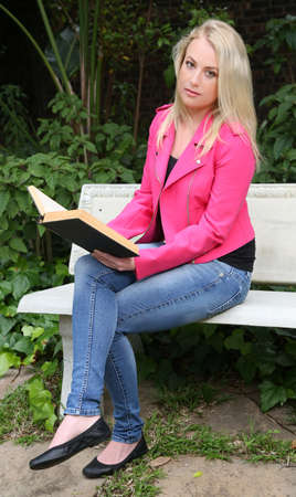 book jacket: Beautiful woman reading a book outdoors while sitting on a concrete bench