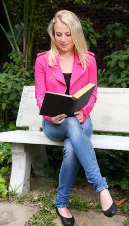 mujer leyendo libro: Hermosa mujer leyendo un libro al aire libre mientras se está sentado en un banco de hormigón