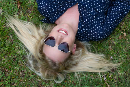 splayed: Lovely young lady relaxing on the grass and wearing heart shaped sunglasses Stock Photo