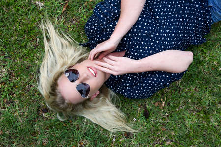splayed: Lovely young lady relaxing on the grass and wearing heart shaped sunglasses and hair splayed