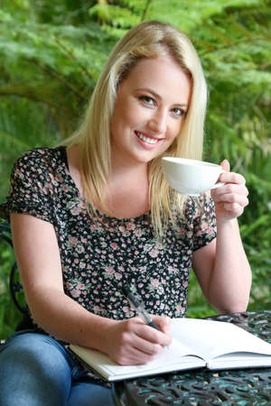 Lovely blond woman writing in her journal while sitting at a table outdoors photo