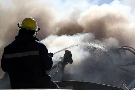 burnt out: Fireman spraying water on a burnt out and smoking vehicle Stock Photo