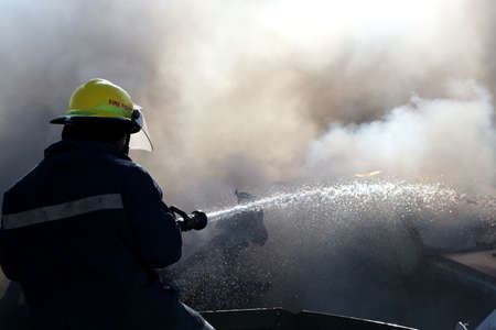 fireman: Fireman spraying water on a burnt out and smoking vehicle Stock Photo