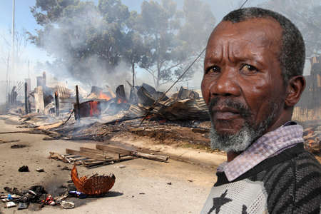 township: African man with worried expression at scene of fire and arson